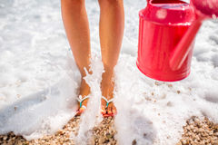 Woman's legs with watering can on the beach Stock Images