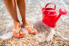 Woman's legs with watering can on the beach Royalty Free Stock Photography
