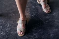 Woman`s legs wearing old sandal shoes. Closeup image of a woman`s legs wearing old sandal shoes , walking and standing on dirty concrete floor Royalty Free Stock Photos