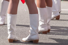 Woman's legs in white boots. Attractive legs of young women in white boots standing on street royalty free stock image