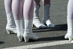 Woman`s legs in white boots. Attractive legs of young women in white boots standing on street royalty free stock images