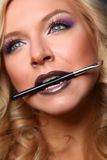 Woman's lips holding make up brush Stock Photo