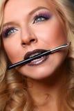 Woman's lips holding make up brush Stock Photo