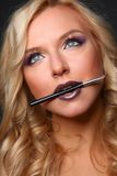 Woman's lips holding make up brush Stock Photos