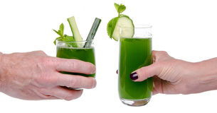 Woman's and man's hand making toast with glasses of cucumber jui Royalty Free Stock Photo