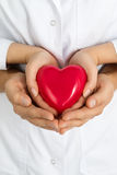 Woman's and man's hands holding red heart together Royalty Free Stock Image
