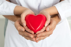 Woman's and man's hands holding red heart together Stock Photo