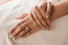 Close up of brides manicure hands and wedding ring stock image
