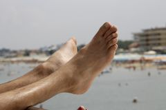 Relaxing feet on a beach holiday. Woman`s or men feet on the coarse sand near the sea. Relaxation at sea in countries with cold climates. Beach vacation holidays stock image