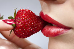 Woman`s mouth with red strawberry stock photo