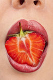 Woman`s mouth with strawberry Stock Images