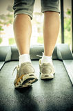 Woman's muscular legs on treadmill Stock Photo