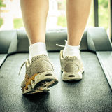 Woman's muscular legs on treadmill Stock Photography