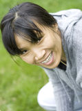 A woman's nice smile. An asian woman shows a nice smile while kneeling in the grass Stock Photography