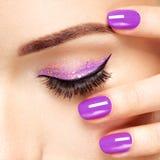 Woman& x27; s oko z fiołkowym oka makeup, gwoździami i Zdjęcia Stock