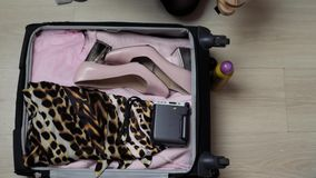 Woman`s open bag on a desktop with clothing and accessories, she is packing and getting ready to leave, travel and