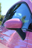 Woman's pink car. Rear view mirror closeup Royalty Free Stock Images