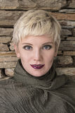 Woman`s portrait blonde. Fashion hairstyle, haircut, makeup in grey shades. Beautiful woman with short hair blonde wearing khaki scarf on stone wall background royalty free stock photos