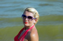 Woman`s portrait in sunglasses against the background of the sea Stock Photography