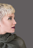 Woman`s profile portrait blonde with fashion hairstyle, haircut, makeup in grey shades. Beautiful woman with short hair blonde wearing khaki scarf on grey stock photography