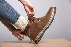Woman's putting on her walking boots. Woman's hands putting on a walking boot with thick socks Royalty Free Stock Photo