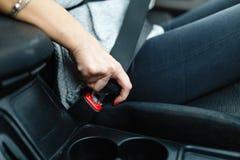 Woman& x27; s ręka przymocowywa z pasem bezpieczeństwa zaczynać jechać na samochodzie zdjęcia royalty free