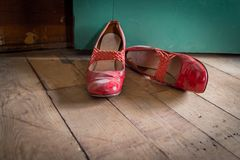 Woman`s red high heel dress shoes lying on rustic wooden floor stock photography