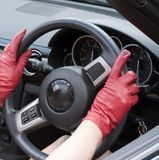 Red leather gloves holding a steering wheel Stock Images