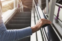 Woman`s right hand on the escalator handrail stock images