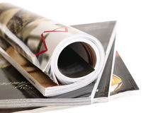 Woman's rolled glossy magazine in stack. Royalty Free Stock Photos