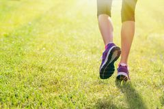 Woman's running shoes on grass Stock Photo