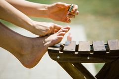Woman`s self pedicure outdoor stock images