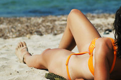 Woman's sexy legs on the beach Stock Images