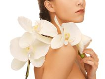 Woman's shoulder and hands holding orchid flower Royalty Free Stock Photos