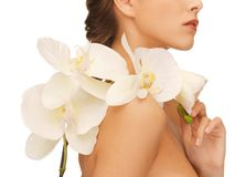 Woman's shoulder and hands holding orchid flower Royalty Free Stock Photography