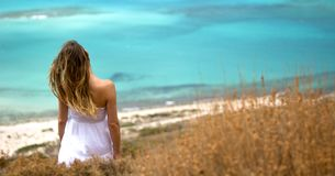 The woman`s shoulders with hair in the wind and white dress Stock Image