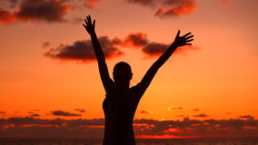 Woman's silhouette in sunset light. Happy girl with raised up hands standing on the beach and enjoying warm summer evening, victory concept Royalty Free Stock Photo