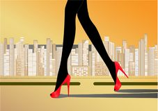 Woman`s slender legs in red high-heeled shoes walk on the road against the yellow background skyscrapers Royalty Free Stock Photo