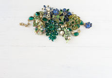 Woman& x27; s-smycken Tappningsmyckenbakgrund Härlig ljus bergkristallbrosch, halsband och örhängen på vitt trä Royaltyfri Fotografi