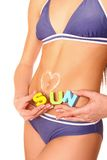 Woman's stomach close-up with sun lotion heart and word sun Stock Photography