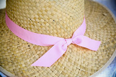 Woman's Straw Sun Hat with Pink Ribbon. A woman's straw sun hut with a pink ribbon. The hat is woven straw and colored light brown Royalty Free Stock Photo