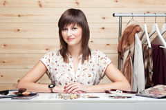 Woman's stylist. With attributes of her work, standing near a coat rack with clothes. Cosmetics and accessories on the table in front of her Stock Images