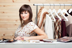 Woman's stylist. With attributes of her work, standing near a coat rack with clothes, cosmetics and accessories on the table Stock Image