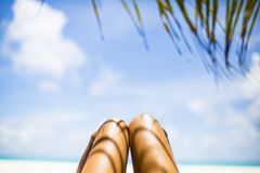 Woman's tanned legs under palm tree on white sandy beach, Maldives Stock Photo