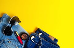 Woman`s Things Elegant Accessories . Jeans lipstick glasses headphones. place for text yellow background summer.  stock image
