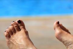 Woman& x27; s voeten met vaag zonnig zwembad op achtergrond Royalty-vrije Stock Afbeelding