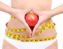 Woman's waist with measuring tape holding apple Stock Image