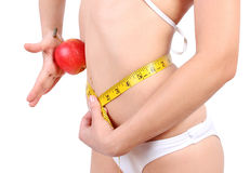 Woman's waist with measuring tape holding apple Royalty Free Stock Image