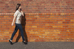 Woman's walk. Young woman walk beside the red brick wall while talking on the phone stock photography