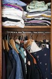 Woman's wardrobe with clothes hanging. Narrow and messy wardrobe with hanging female clothes Stock Photo